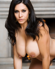 Busty adult star Raylene poses nude in front of a large fireplace, showing off her legendary rack and shapely curves for the Penthouse cameras.